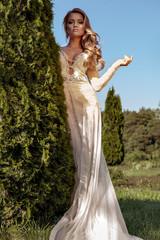 beautiful blonde bride in a luxurious wedding dress in garden