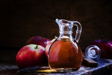 Apple cider vinegar in a glass jug, fresh apples, dark wooden ba