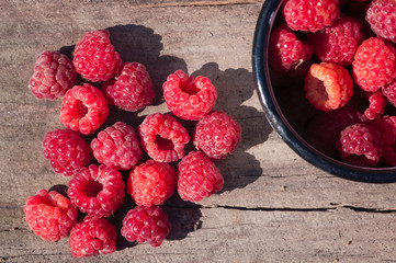 a lot of raspberries in a heart shape on a wooden surface with deep shadows from the sun on outdoors