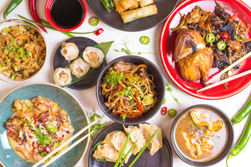 Wall Mural - Assorted Chinese food set. Chinese noodles, fried rice, dumplings, peking duck, dim sum, spring rolls. Famous Chinese cuisine dishes on white table. Top view. Chinese restaurant concept. Asian style