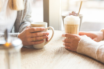 Two beautiful young women in a cafe, drinking coffee and latte macchiato. Close up shot on the hands holding the mugs. Cafe culture concept.