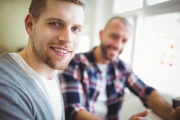 Close-up of happy businessman with colleague in office