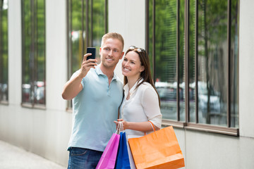 Couple With Shopping Bag Taking Picture In Smartphone