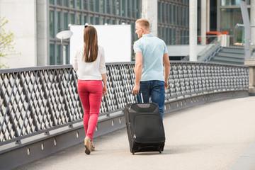 Couple Walking On Bridge With Luggage