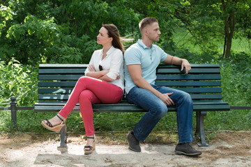 Couple Sitting Back To Back On Bench