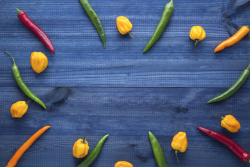 Colorful cayenne chilli peppers, yellow habanero peppers on wooden table with copyspace in the centre. Top view.