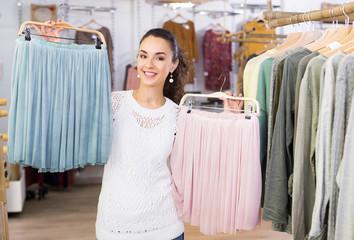 Cheerful female customer buying skirt