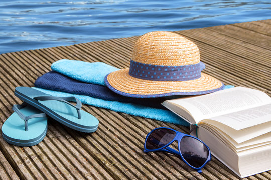 summer vacation, blue water and accessories for beach holidays on a wooden jetty