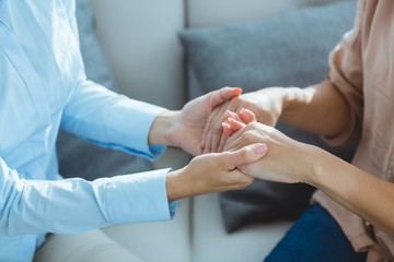 Midsection of therapist holding patient hands