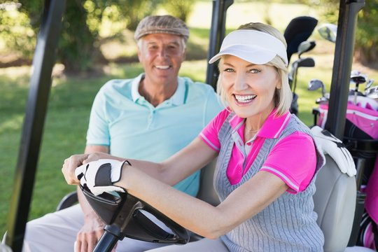 Smiling mature couple sitting in golf buggy