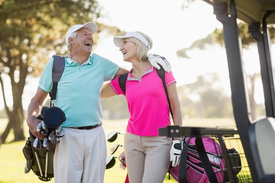 Cheerful mature golfer couple with arm around