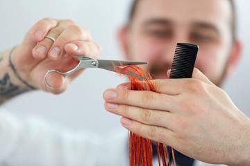 Hairdresser cutting red curls