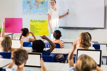 Teacher teaching students using whiteboard