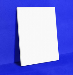 Blank white poster canvas frame leaning at vivid blue concrete p