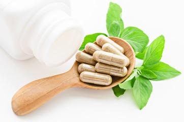 Herbal medicine capsules in wooden spoon.