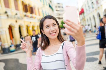 Woman taking photo by mobile phone in Macau city