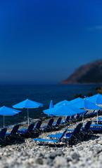 Vertical vivid beach blue umbrellas bokeh background backdrop