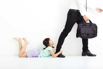 little girl holding her father's legs before go to work
