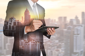 Double exposure of businessman working with tablet, city and sunset as Telecommunication and Technology concept.