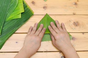 Old woman hand bolting banana leaf on wooden table.