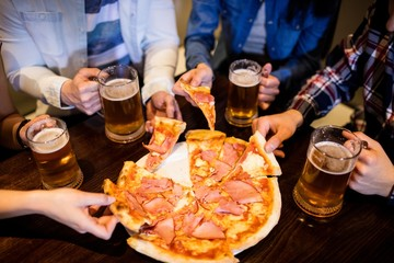 Friends with beer mug and pizza in bar