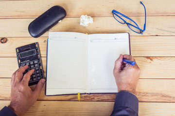 Male hands with calculator and notebook on wooden table