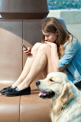 Young woman and her dog golden retriever in the park on a summer day