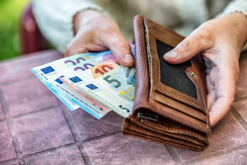 Pensioner woman holding in hands wallet with money.