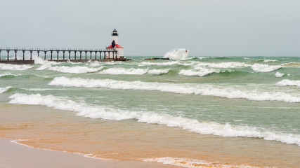 Lake Michigan waves crash against the East Pierhead Outer Lighthouse and catwalk, in Michigan City, Indiana.