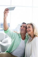 Smiling couple taking selfie at home