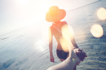 Fotomurais - Young woman in hat guiding a man by the hand into the ocean (intentional sun glare and lens flare effects)
