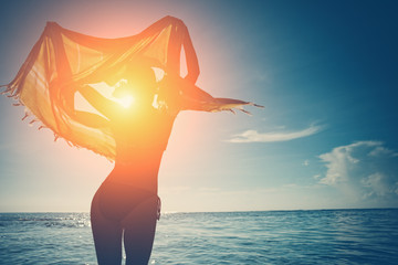 Fotomurais - Woman with shawl standing in the ocean at sunset (intentional sun glare)