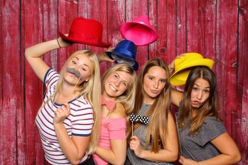 Junge Frauen haben Spaß mit einer Fotobox - Mädchen mit Hüten und Bärte