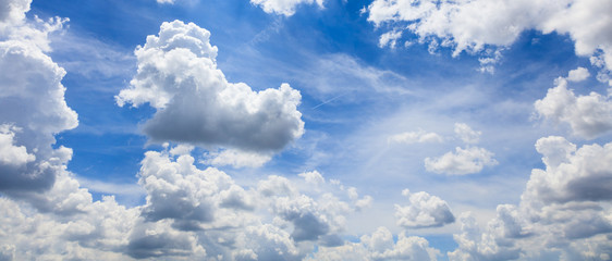 Blue sky with white fluffy clouds background.