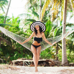 Beautiful tanned luxury young girl sitting in a hammock on the beach, the palm trees in the background a sexy bikini in a wide hat, vacation on a tropical island, healthy skin and hair, perfect body