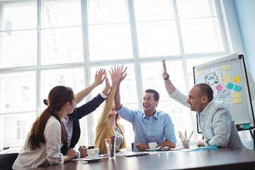 Photo editors high-five in meeting room