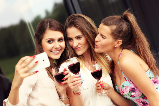 Group of friends with wine taking selfie