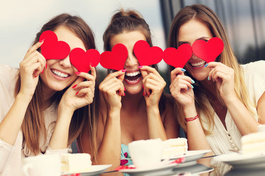 Three girlfriends holding hearts in cafe