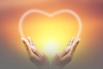 Heart on hands Background blur sunset