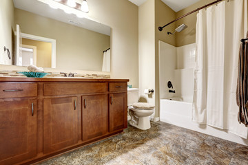 Classic American bathroom with brown cabinets and tile floor.