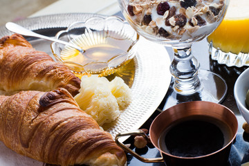 Breakfast assorted yoghurt, granola, coffee, juice, croissant, olives. Appetizer mix with morning dishes. Healthy, fresh, delicious food on dark background. Top view. Copy space.