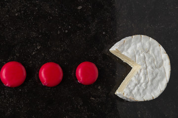 Camembert cheese and mini pieces on black background. Funny game with food, traditional French dish for wine on lunch and dinner closeup.