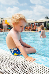 Child sitting on the edge of the pool