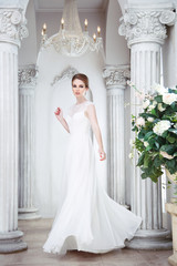 Beautiful bride in a full-length dance in a hall with columns