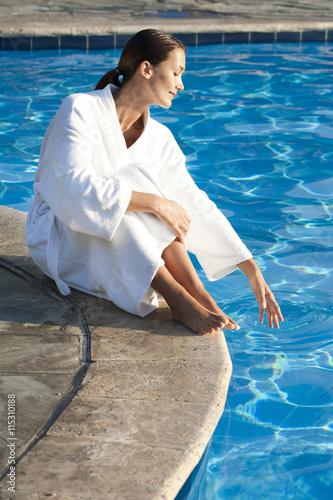 Femme en peignoir assise au bord d 39 une piscine stok for Peignoir piscine