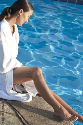 Femme souriant en peignoir assise au bord d 39 une piscine for Peignoir piscine
