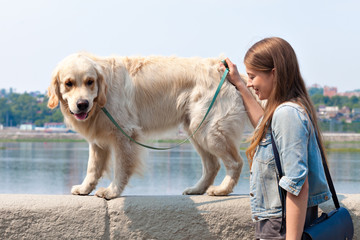 Beautiful young woman and her dog golden retriever in the park