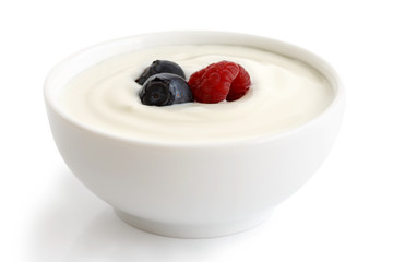 Ceramic bowl of white yoghurt with berries.
