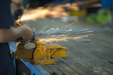 Worker is grinding metal part.