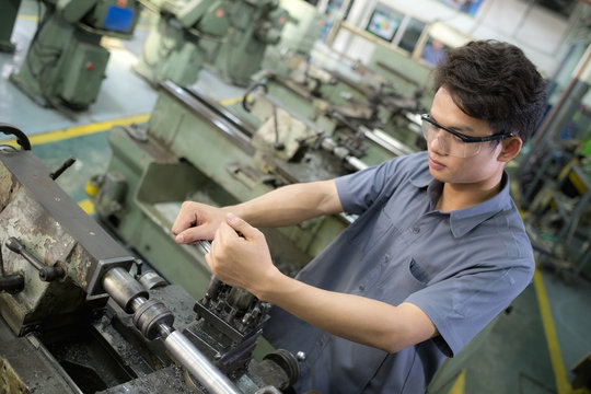 Men are working with machines . Man set up with a steel lathe.